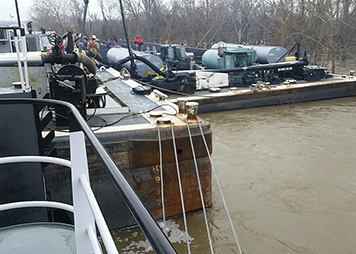 Workers on a river edge pump oil from a damaged barge.