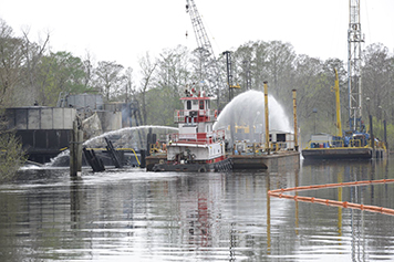 Fire-fighting vessel sprays water on an oil tank on a platform in a bayou.