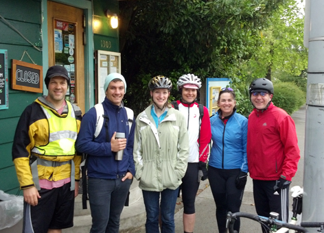 Six people wearing bike helmets standing next to bikes.