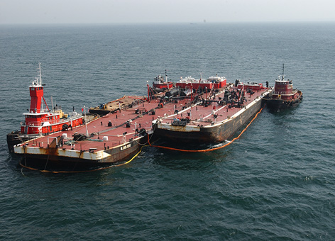 A large barge is being offloaded next to tugboats in the ocean.