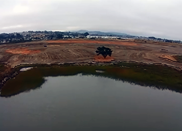 Aerial view of marsh construction site, with berm separating it from the bay.
