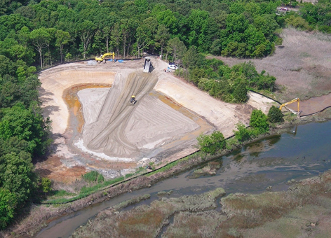Bulldozers prepare a former landfill for restoration along a wetland.
