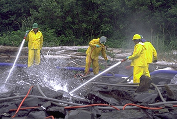 Cleanup workers spray oiled rocks with high pressure hoses.