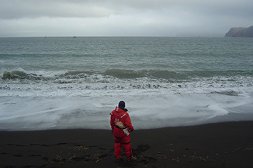 Coast Guard member stands on beach in front of ocean.