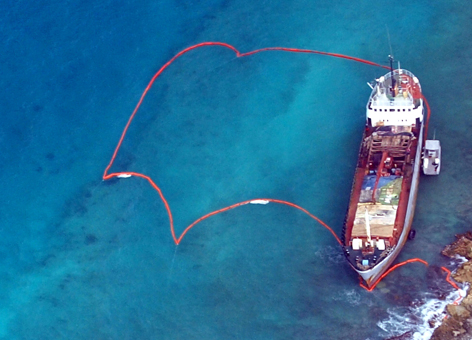 A ship aground on coral reef in Puerto Rico and surrounded by protective boom.