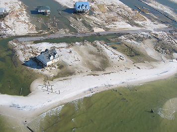 Damaged beachfront homes on a storm-tossed coastal island.