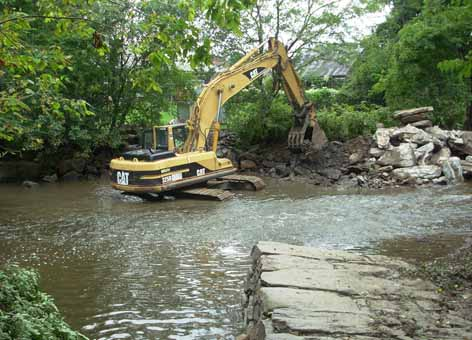 Excavator removes a rock dam from a stream.
