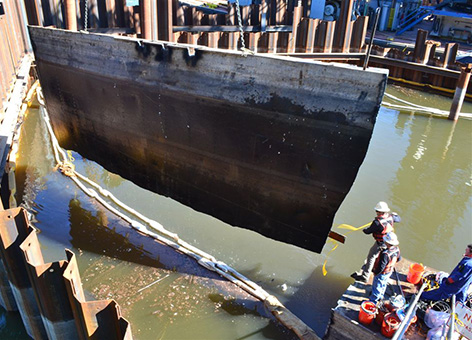A piece of the vessel Davy Crockett is lifted out of the water during salvage.