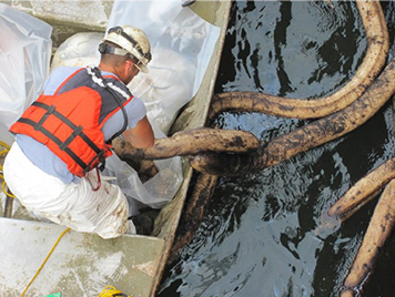 A worker removing oiled sorbent material from inside the cofferdam around ship