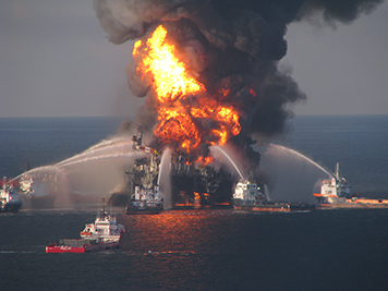 Burning Deepwater Horizon rig with firefighting ships in the Gulf of Mexico.