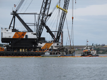 Heavy machinery is brought in to raise a sunken vessel from the sea floor.