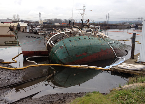 Two rusted ships partially sunk in water and surrounded by containment boom.