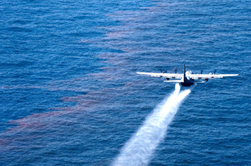 Aircraft flying over oil on water, applying a spray of dispersant.