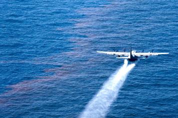 An airplane applies dispersant to an oil spill.