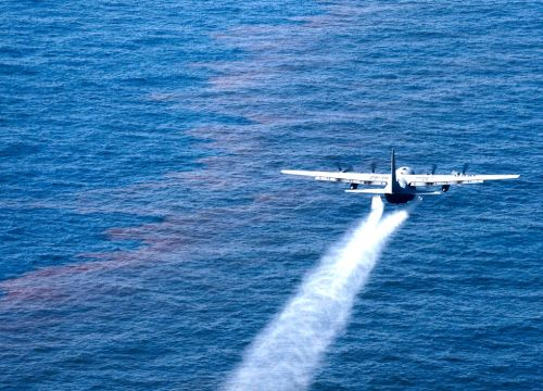 An Air Force plane drops an oil-dispersing chemical onto an oil slick on ocean.