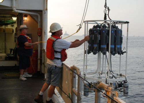 Two people launch a water column sampling device off the side of a ship.