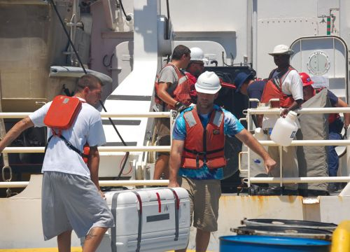 People carrying cases and equipment on a ship.