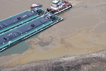 Barge leaking oil in river next to towboat.