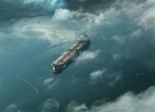 Aerial view of Exxon Valdez tanker with boom and oil on water.