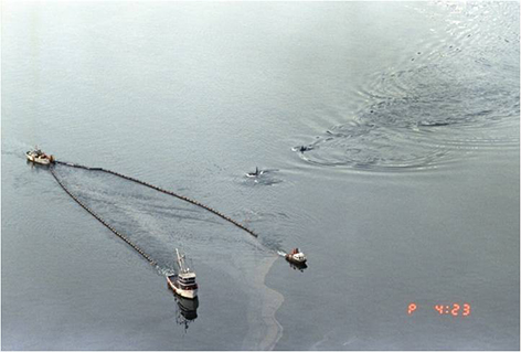 Killer whales swimming alongside skimmers from the Exxon Valdez oil spill.