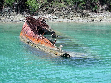 A partially submerged, rusted-out sailboat.