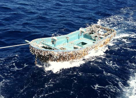 The 20-by-6-foot skiff covered in barnacles is towed behind a fishing vessel.