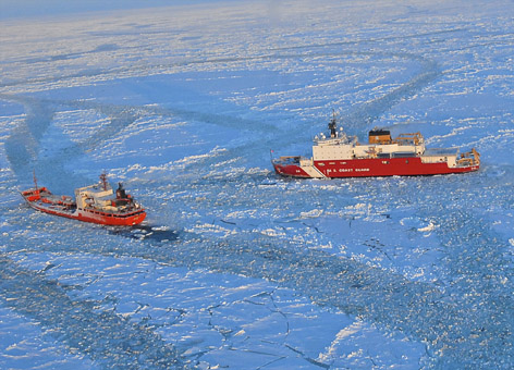 Coast Guard icebreaker breaks ice for a supply ship on an ice-covered ocean.