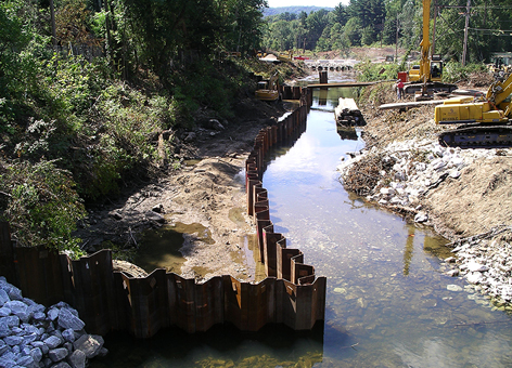 Heavy machinery removes soil and rocks in a polluted stream.