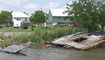 Destroyed dock and debris along a populated canal in Louisiana.