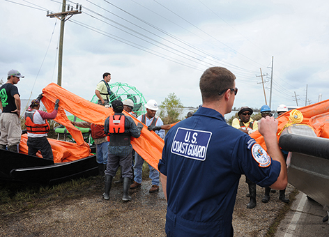 Coast Guard oversees loading of boom onto a response airboat in Lousiana.