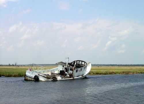 Derelict boat partially submerged in a Gulf of Mexico marsh.