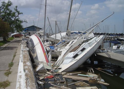 Wrecked sailboats and debris along a dock after a hurricane.