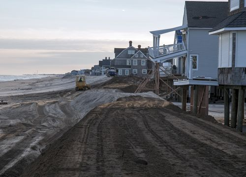 Machines moves sand to rebuild a New Jersey beach by Sandy-damaged houses.