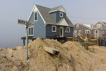 A street sign is buried under huge piles of sand in front of a beach community.