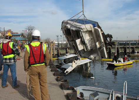 A response team oversees the removal of a sunken boat that was discharging oil.