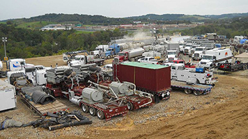 Trucks and heavy machinery used to drill for natural gas parked in dirt.