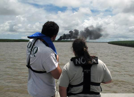 Two people observe smoke and burning in a marsh.