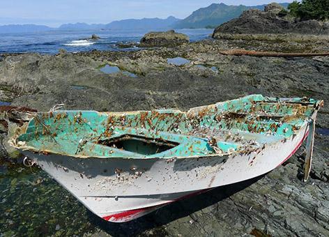 Small boat on rocky shoreline.