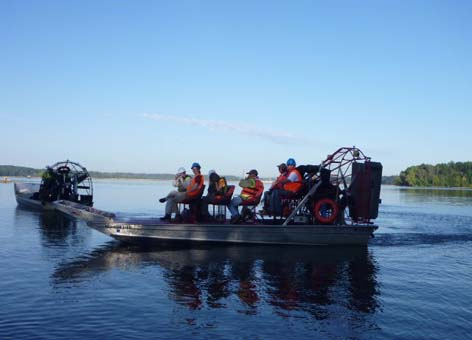 A scientific team monitors cleanup progress in an airboat on the Kalamazoo River