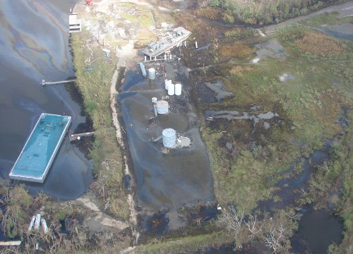 Damaged oil tanks and piping with spilled oil along Gulf Coast.