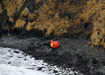 A life raft from grounded rig Kulluk sits on the rocky beach.