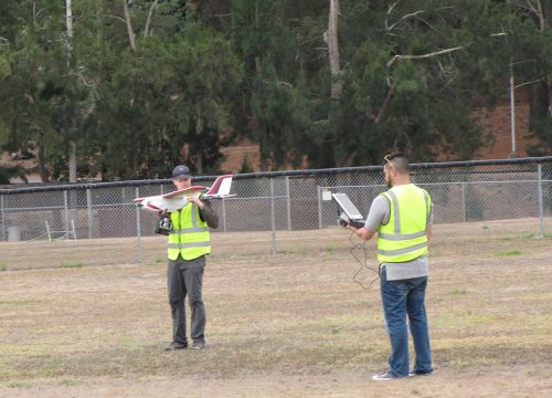 Two men in yellow vests holding a small remote-controlled plane and screen.