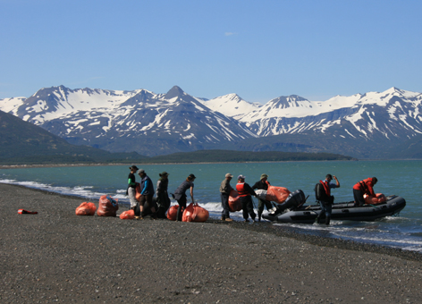 GYRE Expedition participants loading bags of debris from Hallo Bay onto a boat.