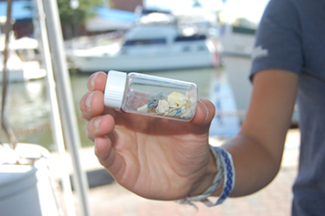 Person holding vial of microplastics.