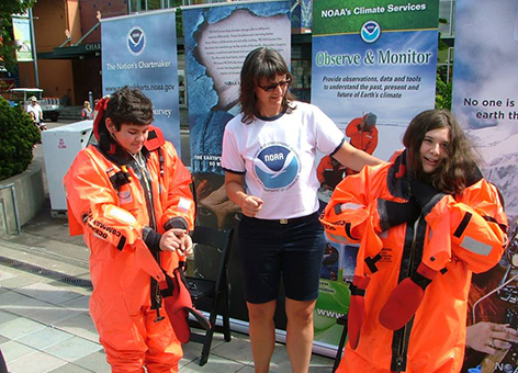 Kids trying on survival suits at the NOAA booth at Seattle Science EXPO Day.