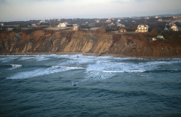 Houses on a cliff overlooking the ocean's pounding surf.
