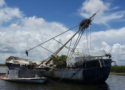 Derelict vessel with osprey nest on top of broken mast.