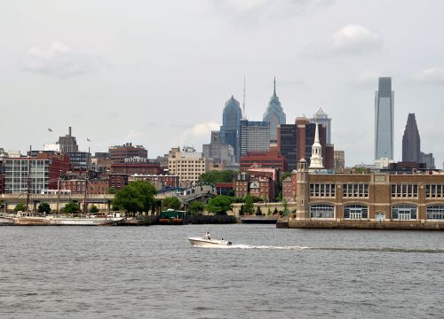 A small boat on the Delaware River with Philadelphia's skyline in the background