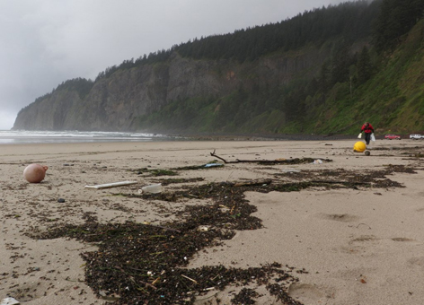 A man picks up plastic floats and debris on an Oregon beach.