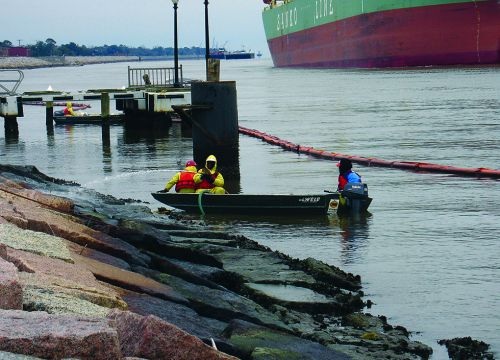 Responders in a small boat pressure-wash rocky shore at the site of an oil spill